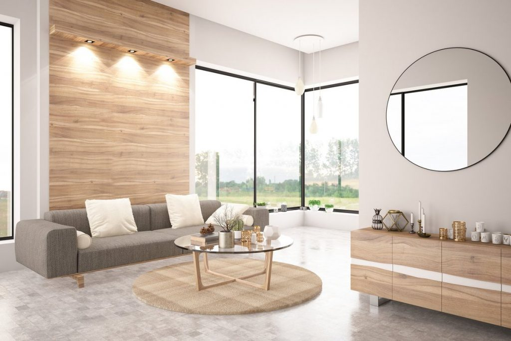 bright room with glass walls, gray sofa, white pillows, and mirror